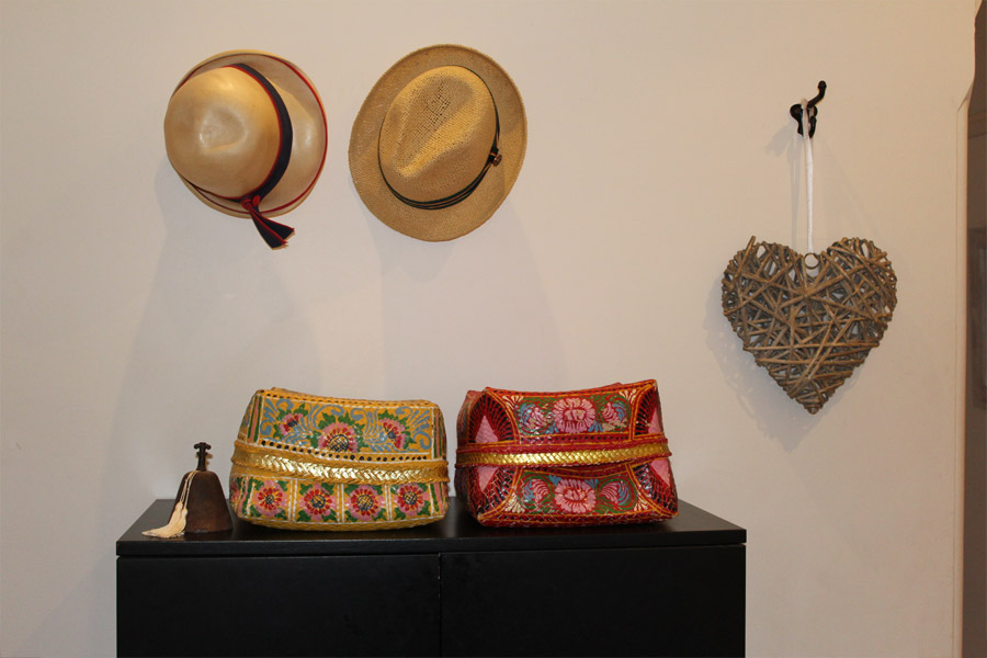 Sun Hats on Hooks close to the front door resemble a Work of Art